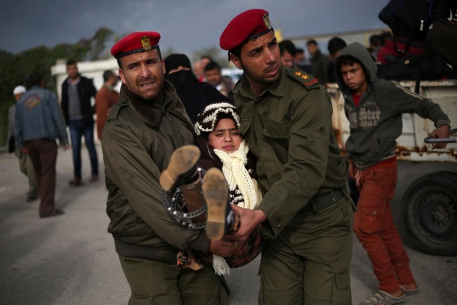 Des officiers palestiniens aident une jeune fille blessée... (PHOTO SAID KHATIB, AFP)