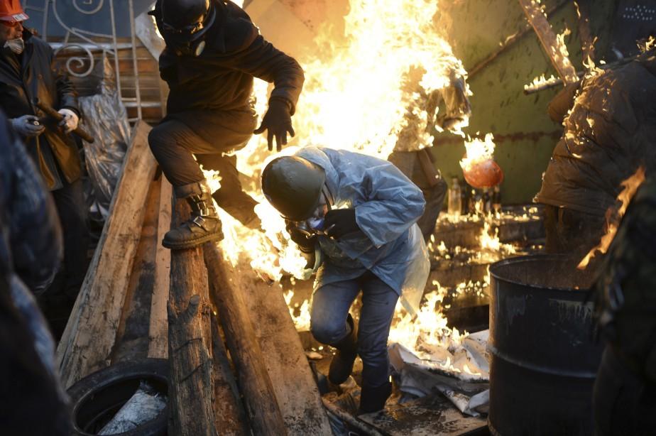 Cette photo datant du 20 février montre des manifestants se protéger des flammes pendant une altercation avec la police, à Kiev. (AFP, Bulent Kilic)