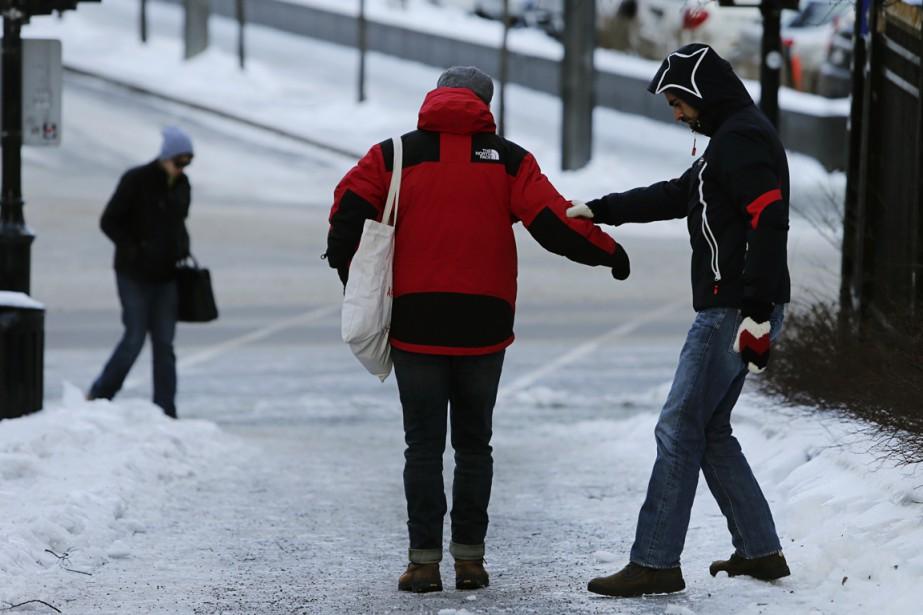 Des piétons se sont entraidés à Montréal pour éviter de glisser sur les trottoirs recouverts de glace. (Photo Martin Chamberland, La Presse)