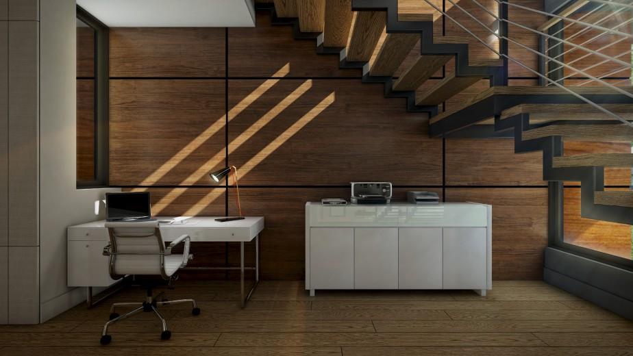 Au rez-de-chaussée, le bureau prend place sous l'escalier dont la structure en U étirée sur toute la hauteur de la maison et encadrée de verre laisse passer la lumière. Au mur, les panneaux acoustiques plaqués bois de la compagnie de Québec Acoustico allient utilité et beauté. (Graph Synergie)