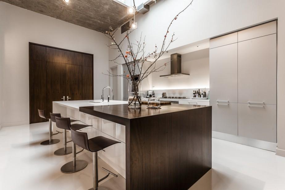 L'îlot est recouvert d'un comptoir en résine acrylique et en bois. Derrière les panneaux, les deux frigos, les deux lave-vaisselle, les deux fours encastrés et la plaque de cuisson au gaz (Photo fournie par Sotheby's)