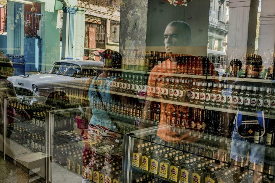 Des passants devant un magasin de rhum, un produit emblématique du pays. (Photo The New York Times)