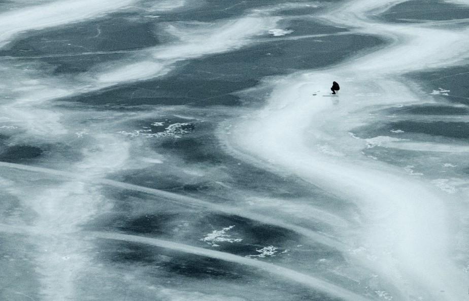 Un pêcheur solitaire mouille sa ligne dans les eaux du lac Ontario. | 25 janvier 2015