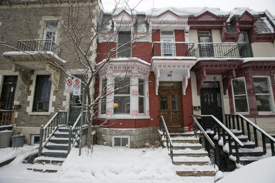 La maison de ville aux boiseries rose et blanche date de 1892. L'entrée de sous-sol est derrière l'escalier, dans une courette anglaise partagée avec le voisin. (Photo David Boily, La Presse)