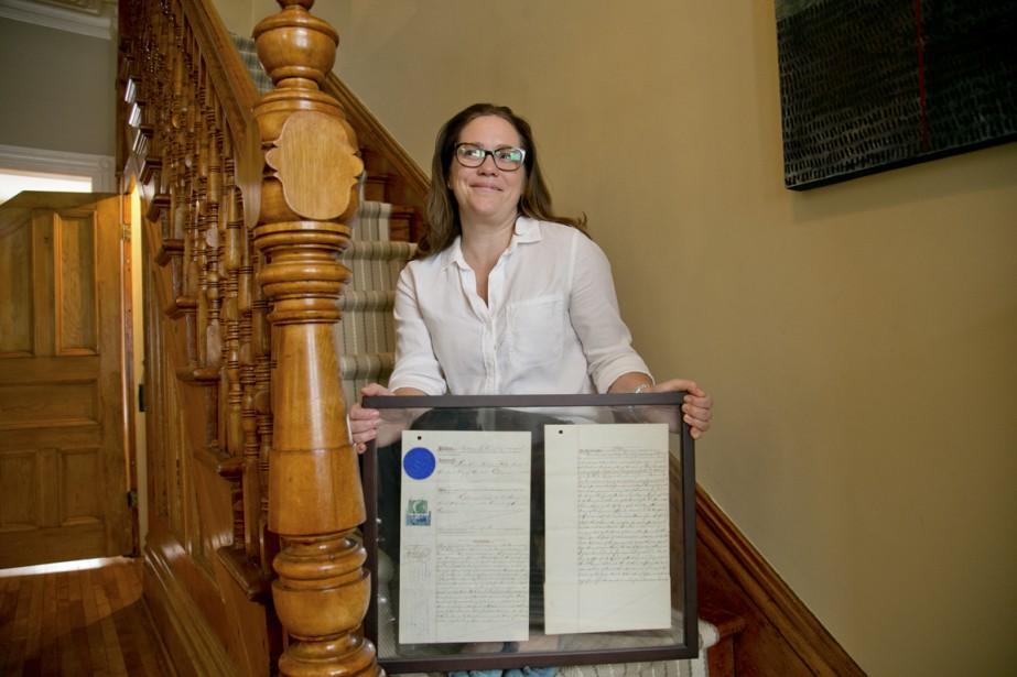 Elizabeth Gomery dans le bel escalier de bois de sa maison. Précieusement encadré: le premier titre de propriété de la maison, héritage d'un électricien du Canadien Pacifique. (Photo David Boily, La Presse)