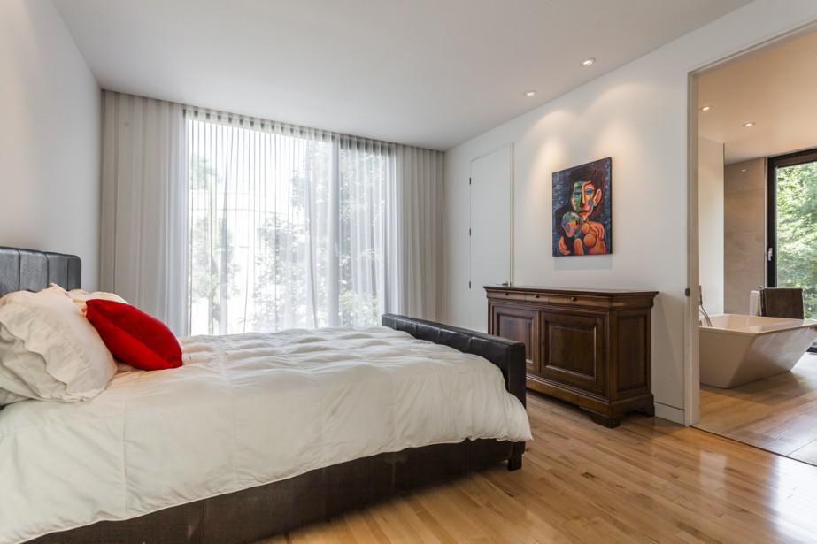 Les portes de la chambre à coucher et de la penderie, à la fois étroites et très hautes, sont pourvues d'un cadre minimal. C'est tout le contraire pour celle menant à la salle de bains adjacente. Une ouverture a été pratiquée au plafond pour cacher le rail des rideaux. (Photo fournie par Sotheby's International Realty Québec)