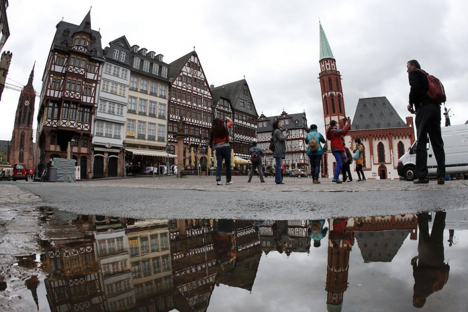 Des touristes arpentent la place Roemerberg à Francfort,... (Photo Michael Probst, Archives AP)