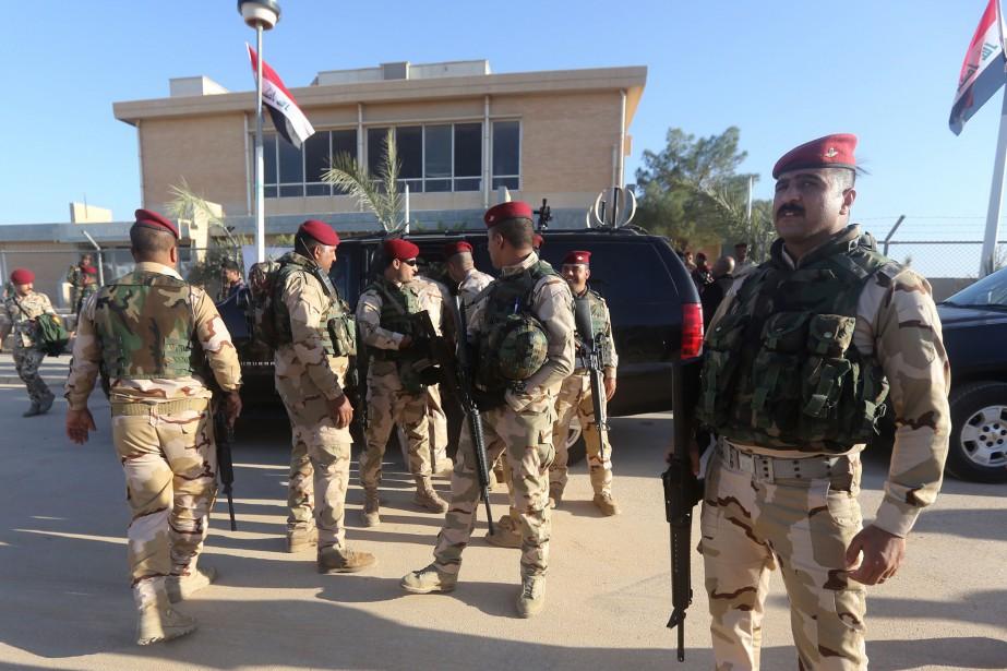 Des combattants irakiens montent la garde devant un... (PHOTO ARCHIVES AFP)