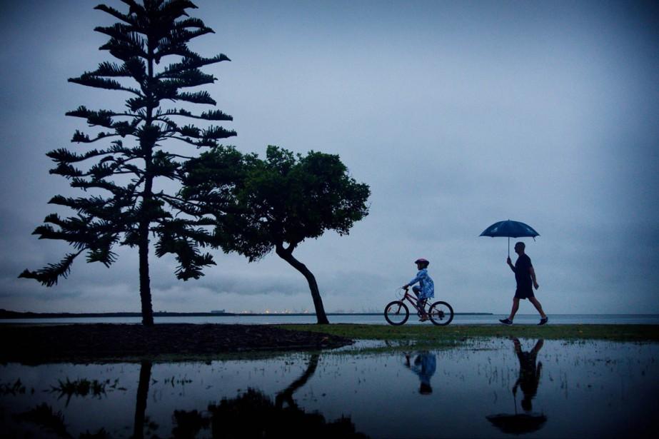 Des résidants de Brisbane marchent sous la pluie... (PHOTO PATRICK HAMILTON, AP)