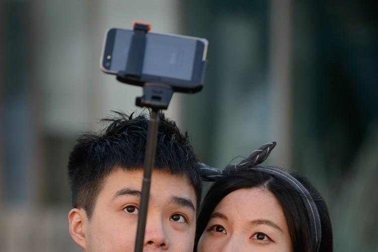 Les «bras pour selfie» dont de plus en plus de touristes se... (Archives AFP)