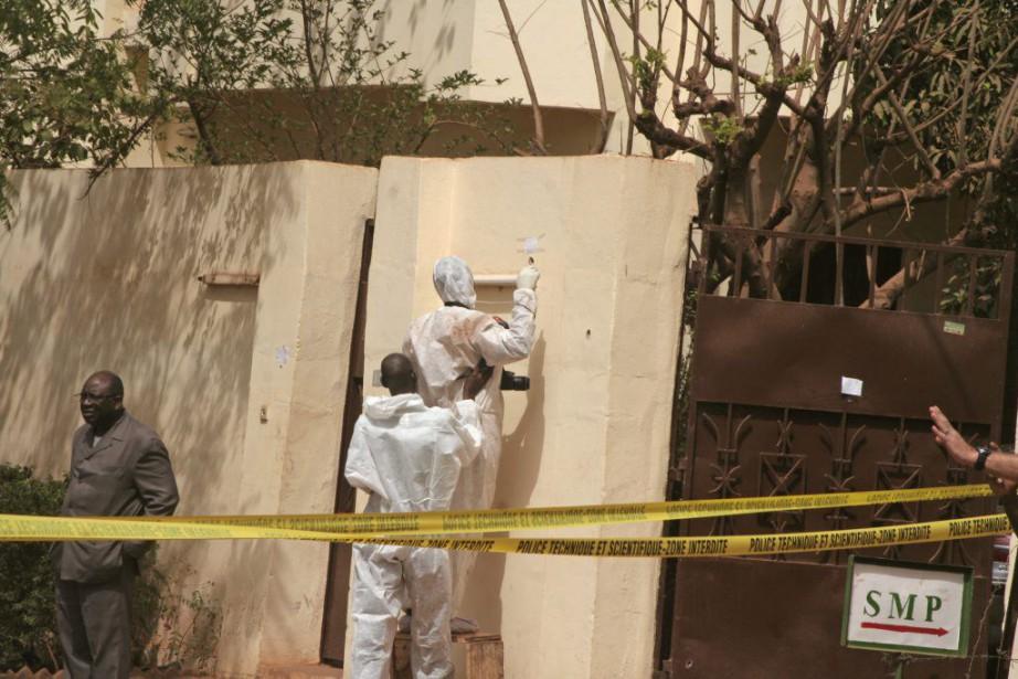 Des enquêteurs étudient la scène de crime, le... (PHOTO HAROUNA TRAORE, AP)