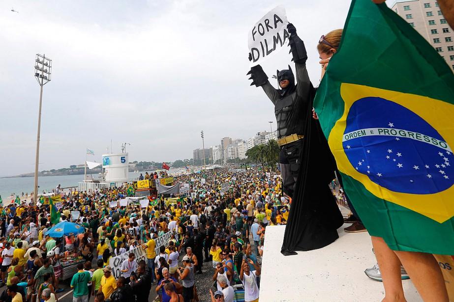 Un manifestant déguisé en Batman tient une pancarte... (PHOTO Ricardo Moraes, REUTERS)