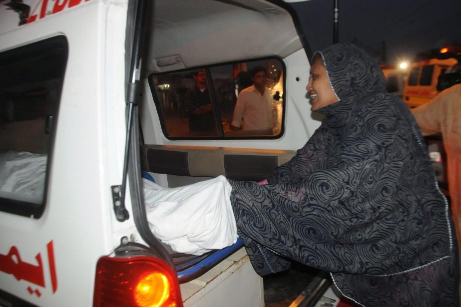 Une femme se recueille près du corps d'un... (Photo Rizwan TABASSUM, AFP)