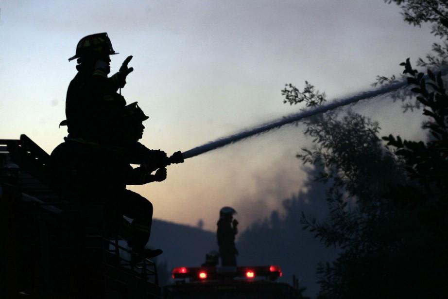 Des pompiers combattent le feu dans la région... (PHOTO LUIS HIDALGO, AP)