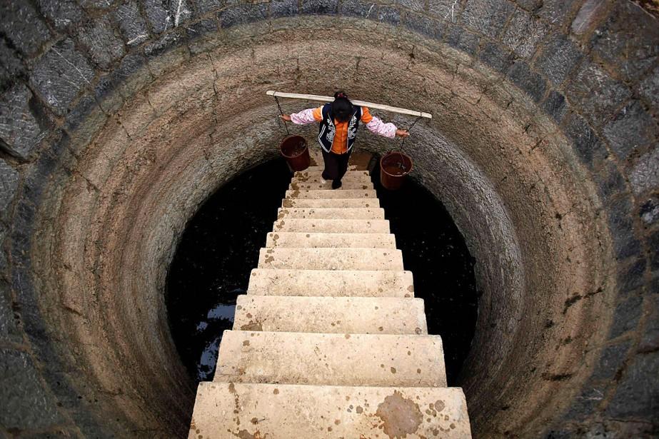 Une femme recueille de l'eau dans un puits... (PHOTO ARCHIVES REUTERS)