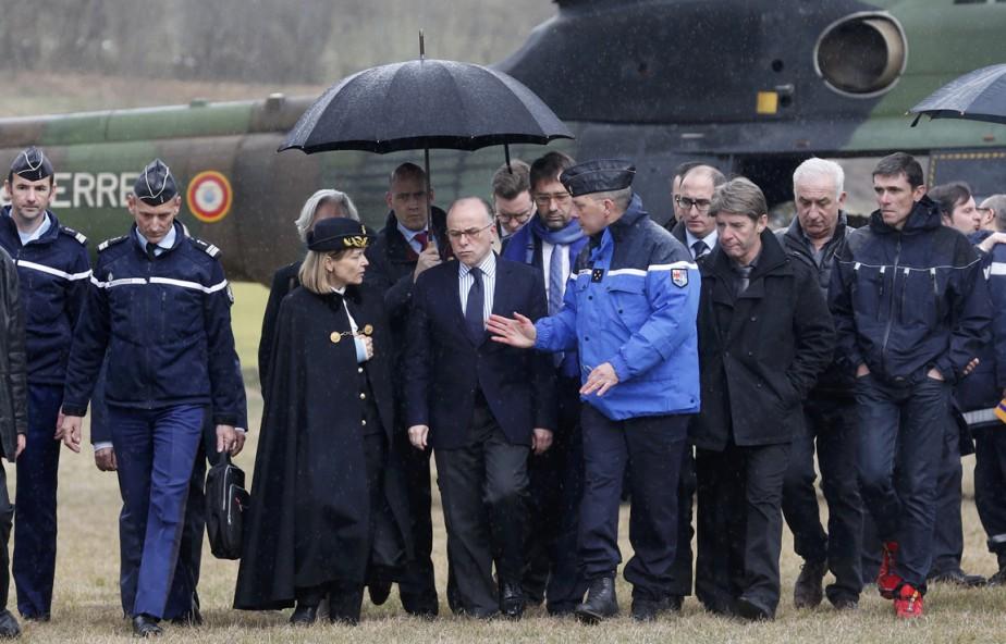 Le ministre français de l'Intérieur Bernard Cazeneuve est informé des derniers développements par un gendarme lors de son arrivée à proximité du lieu du drame. (PHOTO Jean-Paul Pelissier, REUTERS)