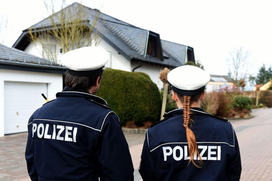 Deux policiers montent la garde devant une maison... (PHOTO PATRIK STOLLARZ, AFP)