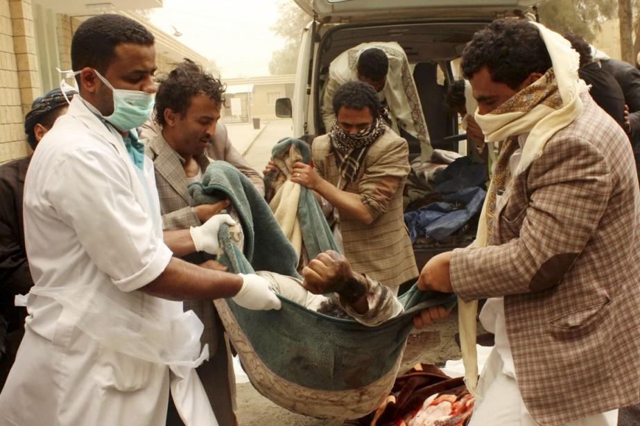 Des secouristes transportent le corps d'une victime civile... (PHOTO NAIYF RAHMA, REUTERS)