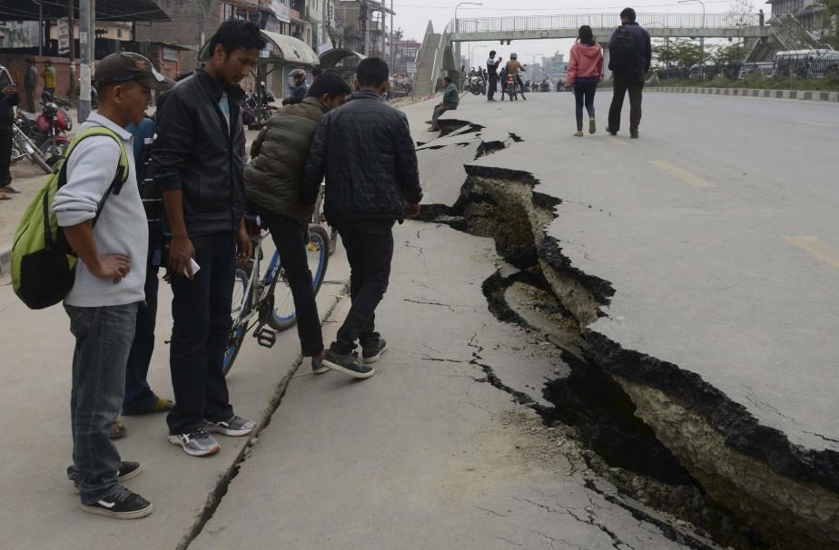 Des témoins regardent la rue détruite par le tremblement de terre. (Agence France-Presse)