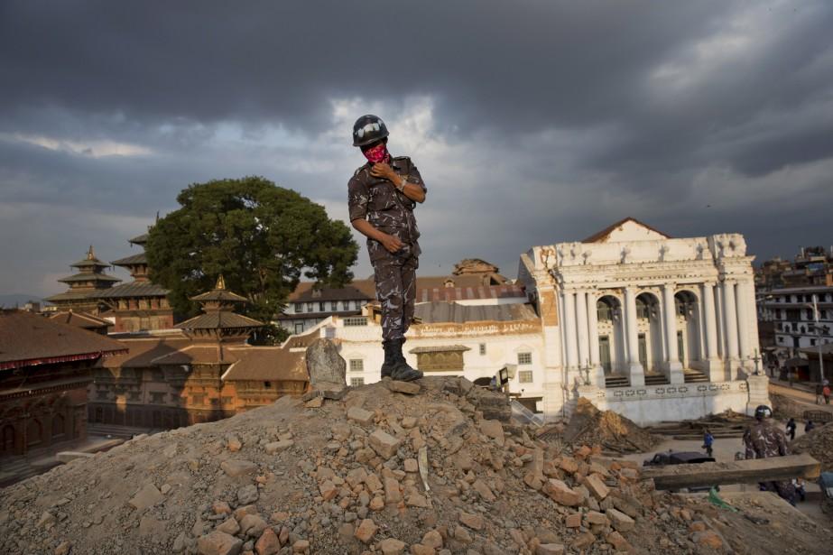 Un policier se tient sur un monticule de débris au Carré Basantapur Durbar, à Katmandou. (Associated Press)