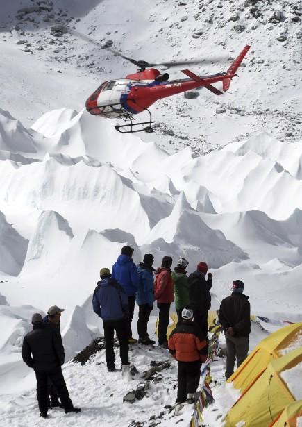 Des sherpas regardent l'hélicoptère de secours alors qu'il décolle avec l'un des leurs. (Agence France-Presse)
