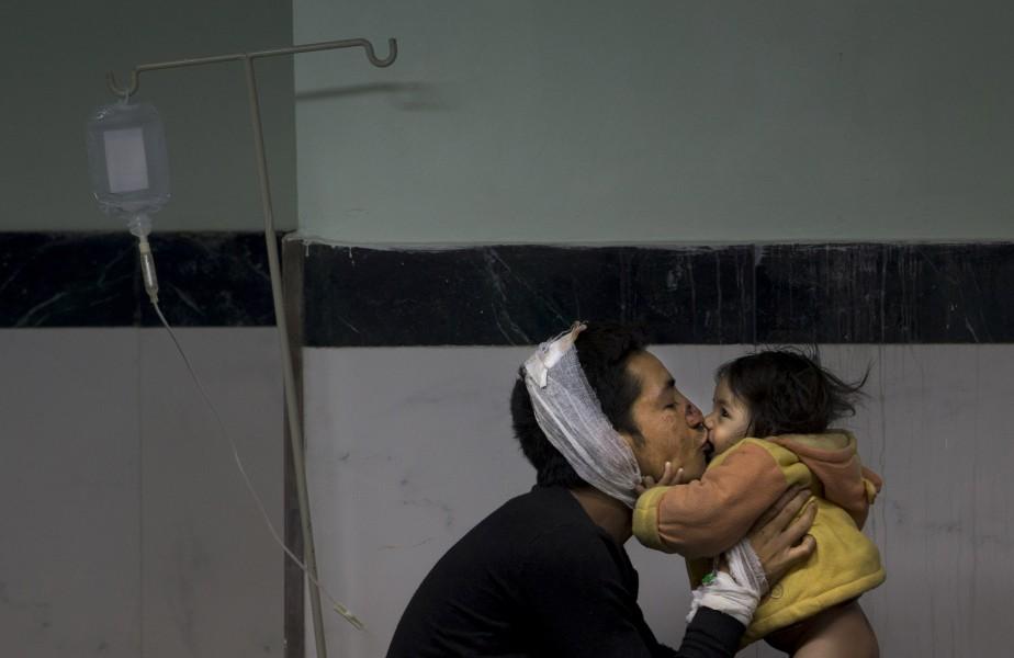 Un homme embrasse son bébé après avoir reçu des soins. (Associated Press)