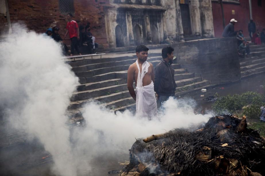 Des gens surveillent un bûcher funéraire. (Associated Press)