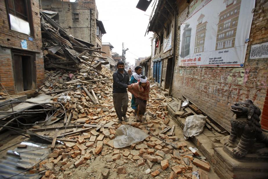 Une vieille femme blessée marche dans les décombres après avoir été soignée à Bhaktapur, près de Katmandou. (Associated Press)
