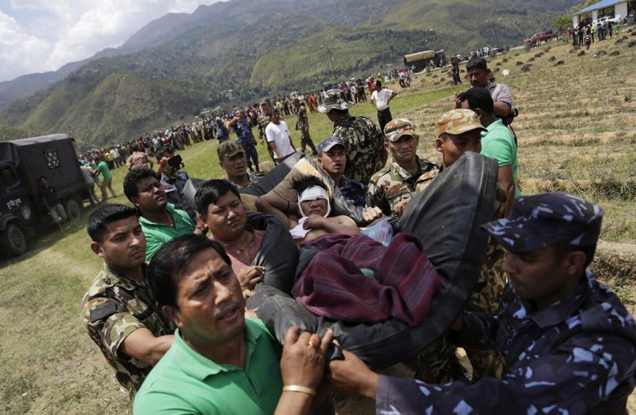 Des soldats et secouristes népalais transportent un blessé sur une civière vers un hélicoptère de l'armée indienne, à Trisuli Bazar. (PHOTO Altaf Qadri, AP)