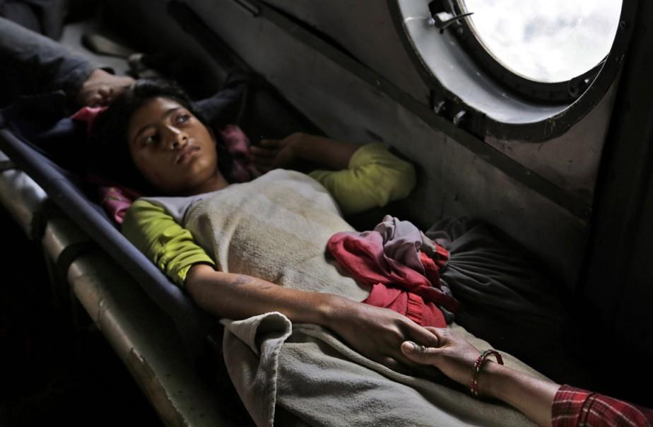 Une jeune fille blessée dans le séisme de samedi tient la mère de sa main alors qu'elle est évacuée à bord d'un hélicoptère de l'armée de l'air indienne de la ville de Trisuli Bazar vers la capitale Katmandou, le 27 avril. (PHOTO Altaf Qadri, AP)