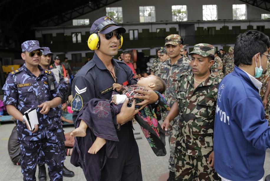Un membre des forces de l'air indiennes tient dans ses bras un bambin blessé, à l'aéroport de Katmandou, le 27 avril. (PHOTO Altaf Qadri, AP)