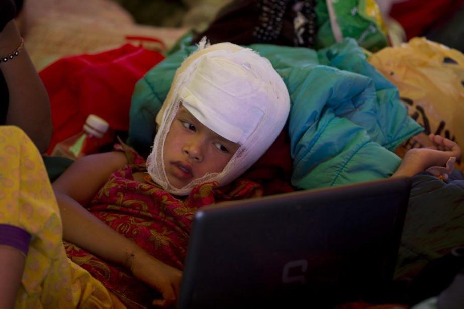 Une fillette blessée lors du séisme regarde un... (PHOTO MANISH SWARUP, AP)