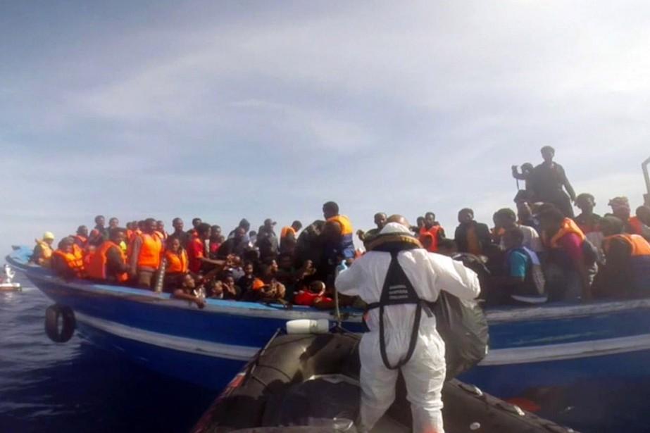 Des gardes-côtes italiens portent secours à des migrants... (PHOTO AFP/GUARDIA COSTIERA)