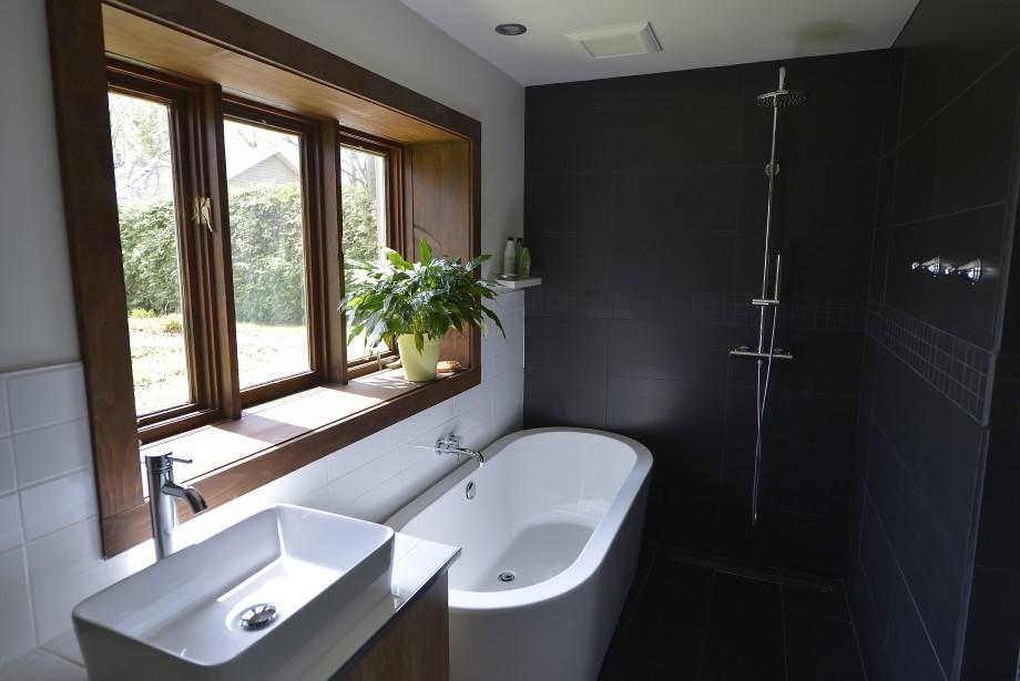 La céramique noire mate enserre une douche italienne à jet de pluie. La fenêtre est d'origine. (Le Soleil, Yan Doublet)