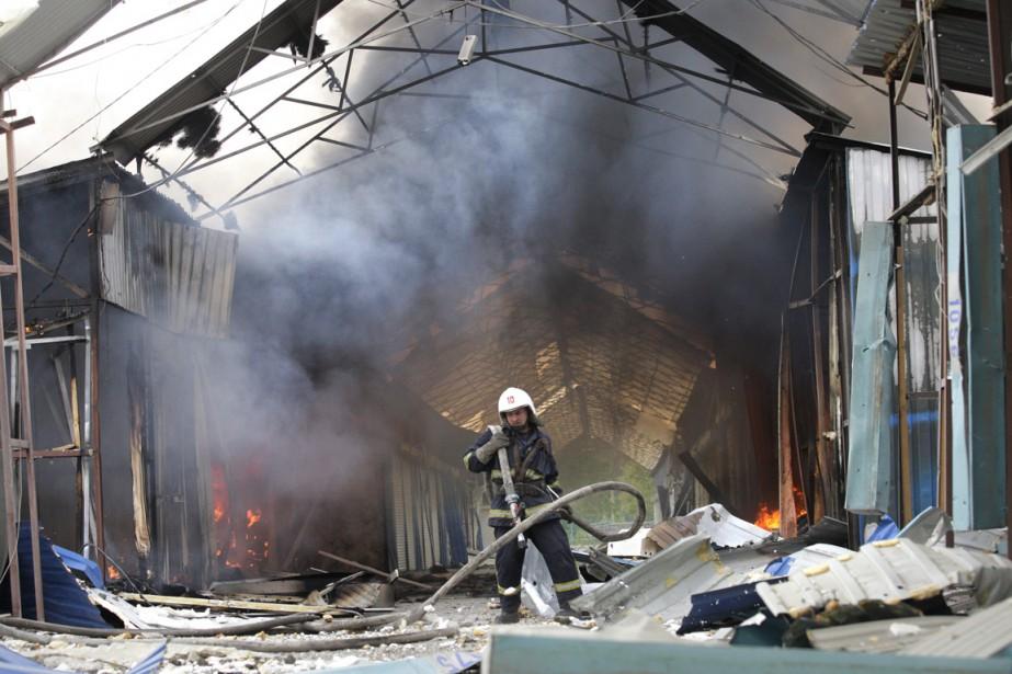 Un pompier s'affaire à éteindre un incendie dans... (PHOTO ALEXANDER ERMOCHENKO, AP)