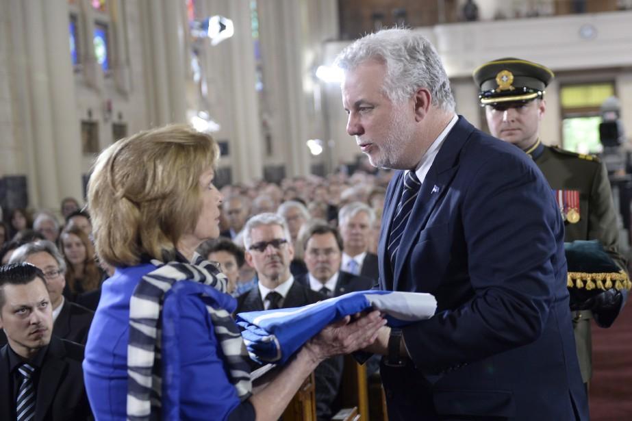La veuve de Jacques Parizeau, Lisette Lapointe, reçoit un drapeau fleurdelisé des mains du premier ministre Philippe Couillard. (La Presse Canadienne, Paul Chiasson)