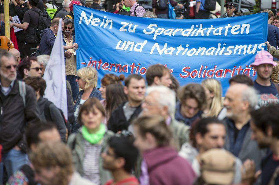 Des manifestants brandissent une banderole où il est... (PHOTO HANNIBAL HANSCHKE, REUTERS)