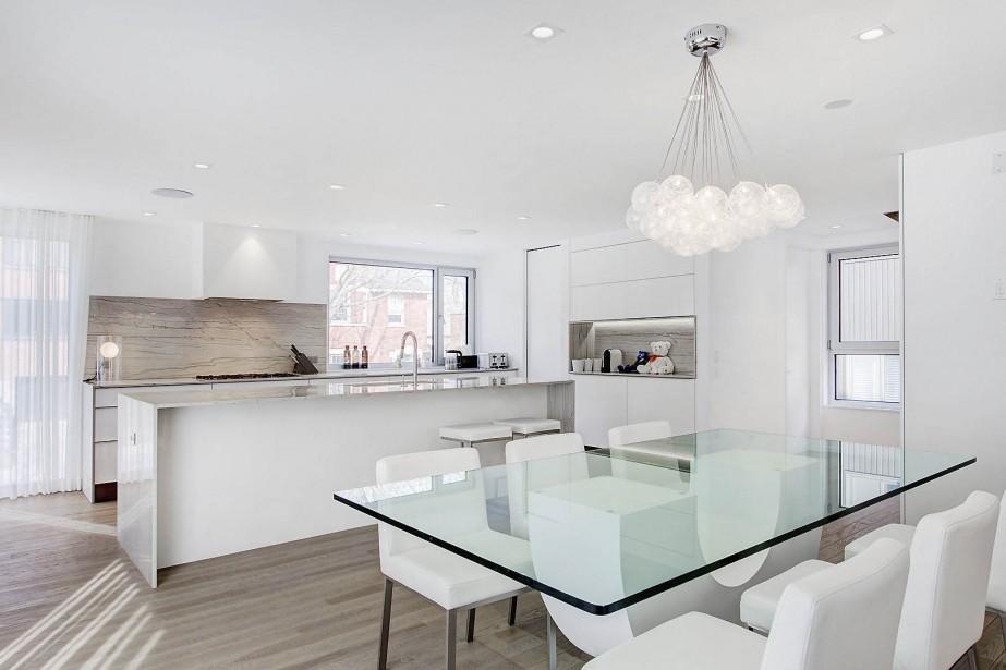 La cuisine partage l'espace avec la salle à manger sur ce palier afin de créer une aire propice à recevoir les gens de manière décontractée. Aussi a-t-on aménagé les fours et le réfrigérateur dans un endroit où on les fait disparaître derrière une porte! (Photo fournie par Groupe Sutton)