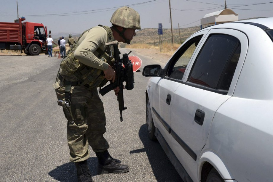 Un soldat turc inspecte une voiture à un... (PHOTO ILYAS AKENGIN, AFP)