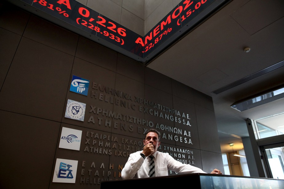 Un employé observe le tableau électronique affichant les... (PHOTO YIANNIS KOURTOGLOU, REUTERS)