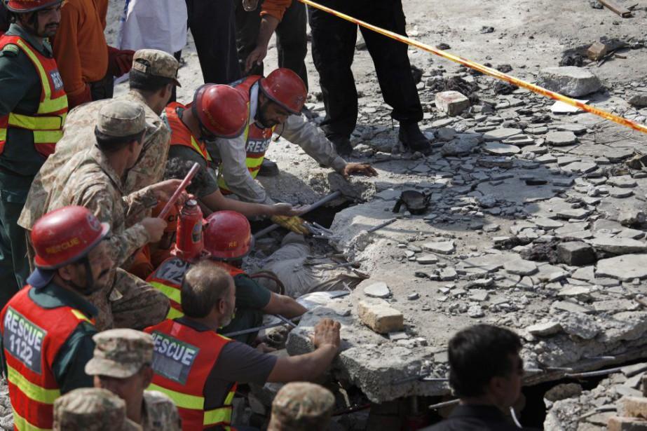 Des secouristes tentent d'extirper le corps d'une victime.... (PHOTO ANJUM NAVEED, AP)