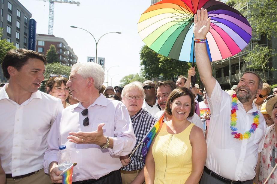 Justin Trudeau, Gilles Duceppe, Thomas Mulcair et Elizabeth May (absente sur la photo) ont participé au défilé de la fierté gaie à Montréal le 16 août. L'absence de Stephen Harper à l'événement a été remarquée. (La Presse Canadienne, Graham Hughes)