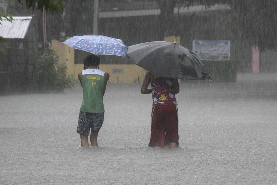 Deux personnes affrontent la pluie dans les rues... (PHOTO TJ CORPUZ, REUTERS)