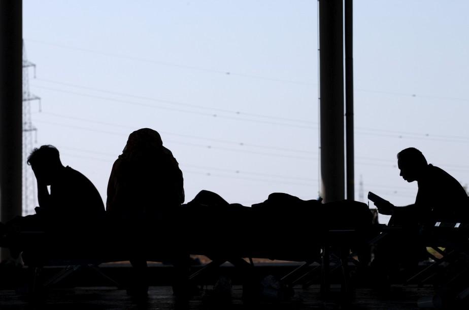 Des migrants attendent dans un camp de fortune... (Photo Heinz-Peter Bader, Reuters)