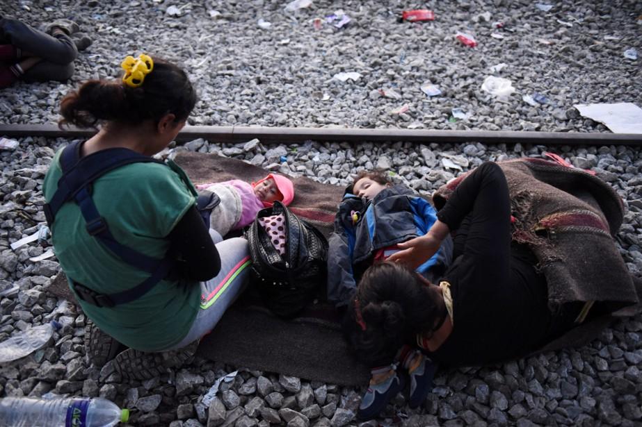 Deux femmes accompagnées de jeunes enfants attendent l'autorisation... (PHOTO GIANNIS PAPANIKOS, AP)