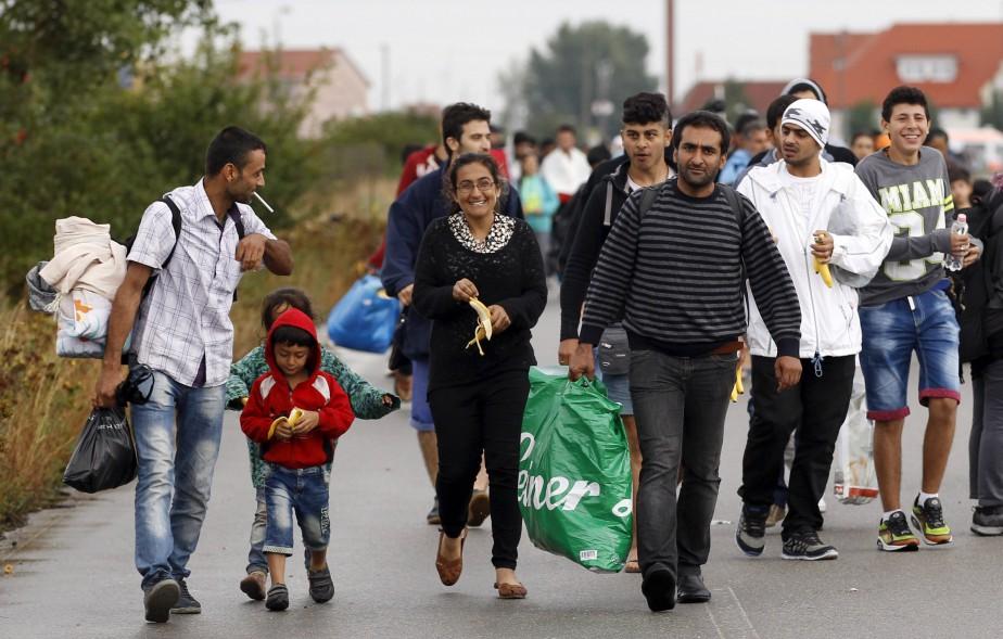 Des migrants traversent la frontière entre la Hongrie et l'Autriche. L'Autriche et l'Allemagne ont ouvert leurs frontières aux réfugiés syriens. (5 septembre) | 5 septembre 2015