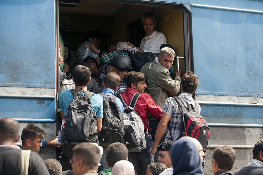 Des migrants se bousculent pour monter à bord... (PHOTO ROBERT ATANASOVSKI, AFP)