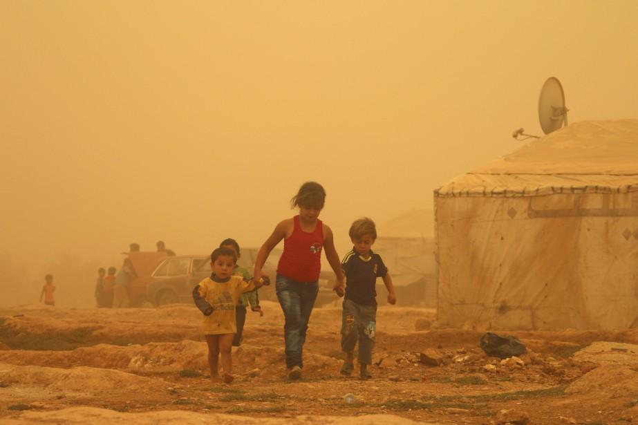Des enfants syriens marchent dans la poussière durant une tempête de sable dans un camp de réfugiés, près de la ville libanaise de Baalbek. (7 septembre) | 7 septembre 2015