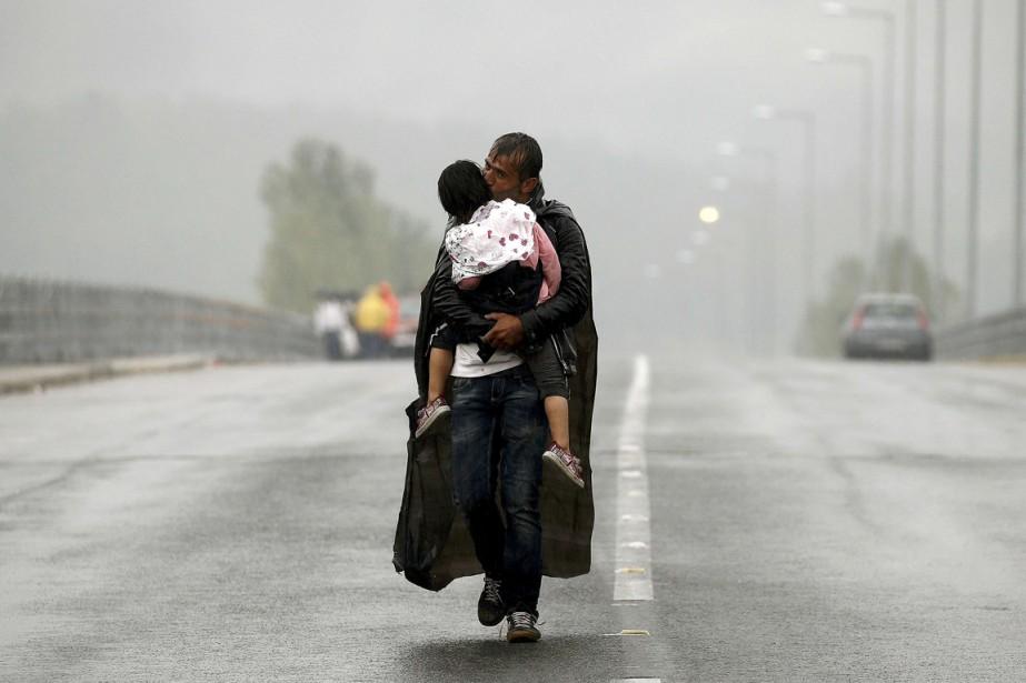 Un père traverse, avec sa fille, sous la... (Photo Yannis Behrakis, Reuters)