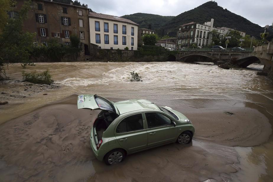 Une voiture est sur le point d'être engloutie par une inondation, à Lodeve, en France, le 13 septembre. | 13 septembre 2015